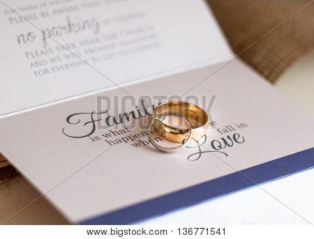 Wedding rings sat on a wedding invitation