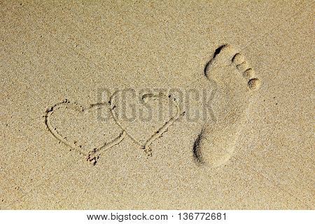 Heart and Prints of legs on sand