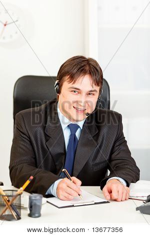 Smiling business man with headset sitting at office desk and taking notes on paper