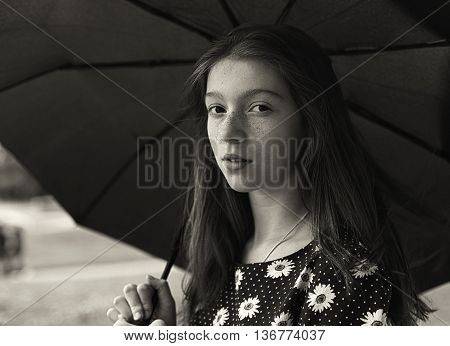 Black and white portrait of a pretty girl with freckled. Standing under umbrella.