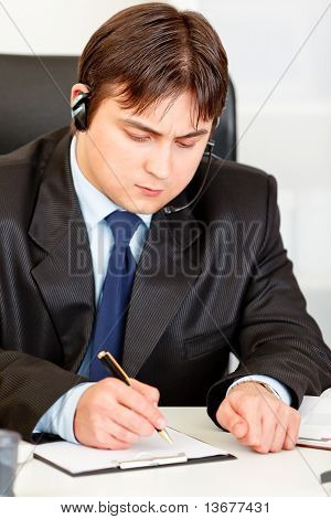 Concentrated business man with headset sitting at office desk and taking notes on paper