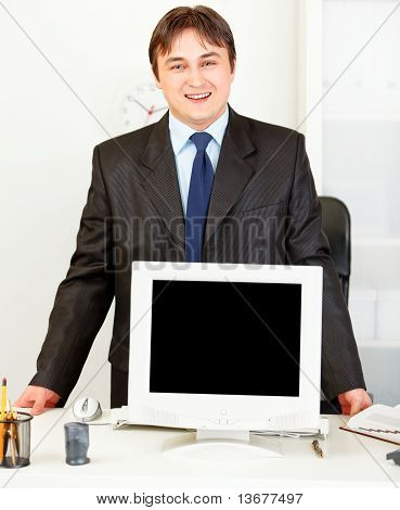 Smiling business man standing at office desk and showing monitors blank screen