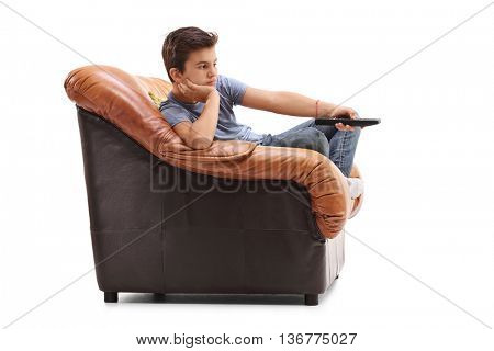 Bored little kid changing channels on television seated in an armchair isolated on white background