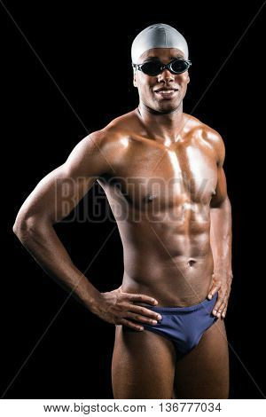 Swimmer standing with hand on hip on black background