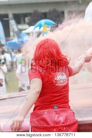 STOCKHOLM SWEDEN - MAY 22 2016: Woman wearing red clothes squirting pink color powder in the Color Run Event in Sweden May 22 2016