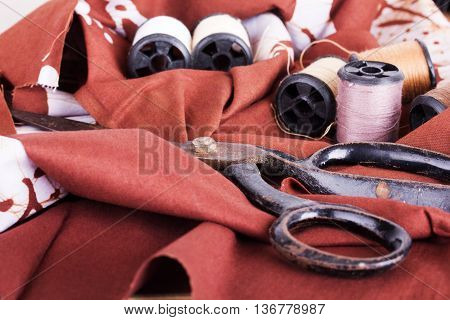 Scissors And Cotton For Sewing On Brown Material