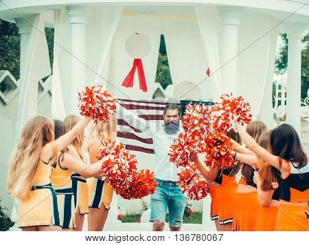 young patriotic happy bearded man with long blue beard holding american flag outdoor celebrating independence day usa with cheerleader team dancing with pompons