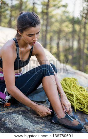 Woman preparing rock climbing sitting on a rock