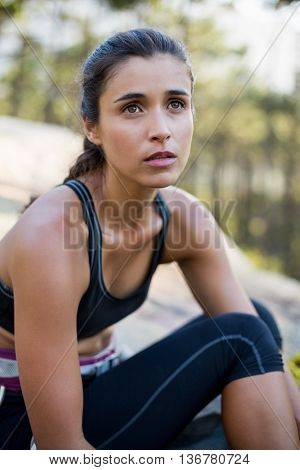 portrait of a woman looking up with climbing equipment sitting on a rock