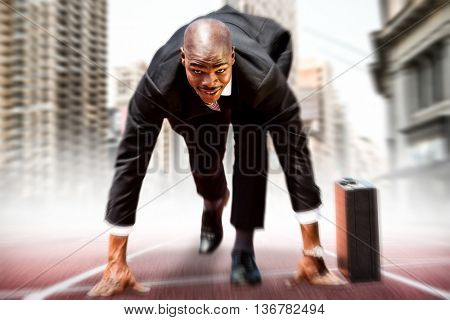 Businessman in the starting blocks against composite image of racetrack in city