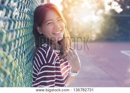 beautiful asian younger woman laughing with happiness emotion and sun light behind