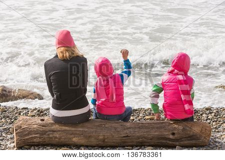 Two Girls And Woman Sitting On A Log On The Beach And Throwing Stones Into The Water