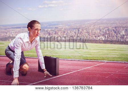 Businesswoman in starting position against composite image of racetrack in city