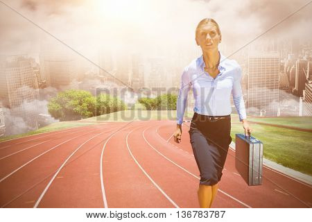 Businesswoman walking with briefcase against composite image of racetrack in city