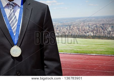 Close up of businessman chest with medal against composite image of racetrack in city