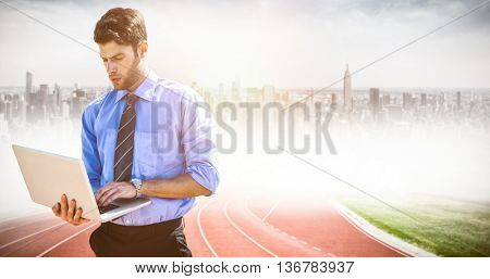 Businessman using a laptop against composite image of racetrack in city
