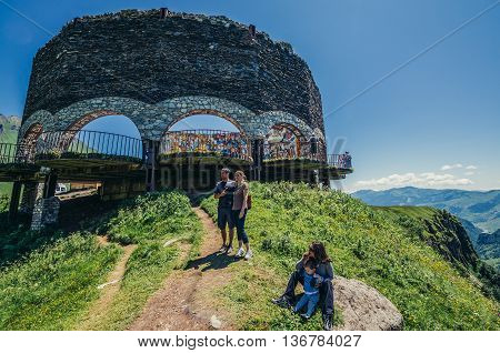 Caucasus Mountains Georgia - July 20 2015. Tourists next to Soviet and Georgian Friendship monument near Guduari ski resort in Georgia in Caucasus Mountains