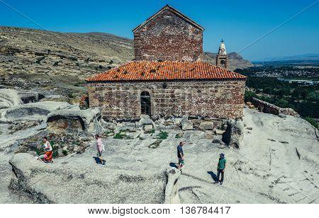 Uplistsikhe Georgia - July 21 2015. Tourists visits Christian Basilica in ancient rock-hewn town called Uplistsikhe in Georgia