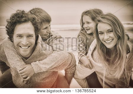 Portrait of a happy couple piggybacking their kids at the beach