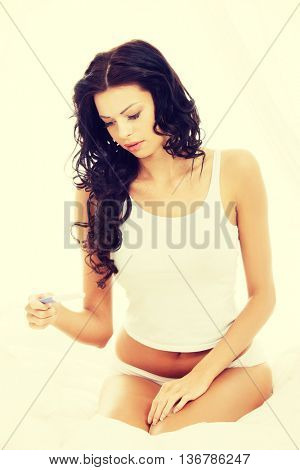 Stressed woman sitting on a bed with the pregnancy test.