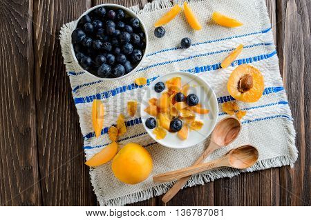 Yogurt with fresh blueberries corn flakes and apricots on a textural brown surface top view
