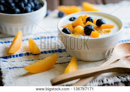 Yogurt with fresh blueberries corn flakes and apricots on a textural brown surface