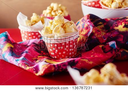 A red paper cup with popcorn against orange background,shallow Depth of Field,Focus on popcorn.