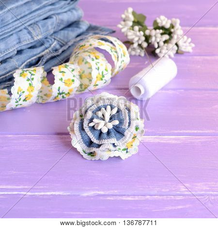 Cute flower brooch made from recycled old jeans, lace and artificial stamens. Summer denim brooch, jeans, thread, needles, pins, lace on lilac wooden background. Creative hobby