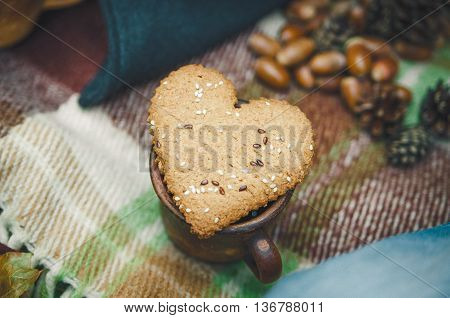 Two Heart Form Cookie is on the Wool Plaid with Autumnal Leaves and Acorn.Selective Focus.Toned