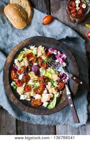 Healthy traditional italian meal: panzanella salad with sun dried tomatoes, green salad leaf, dry ciabatta bread and fresh white cheese served in authentic wooden bowl. Table top view