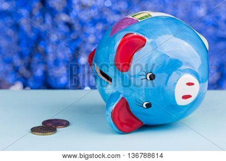 Blue piggy bank on a blue background: it's on its side with a few penny's, a concept of a tight budget