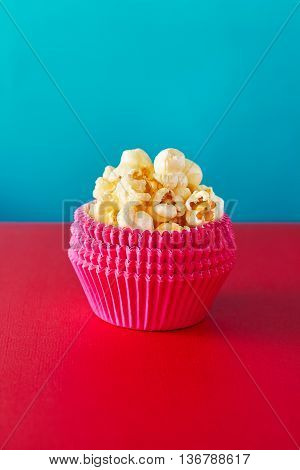 A red paper cup with popcorn against vibrant background,shallow Depth of Field,Focus on popcorn.