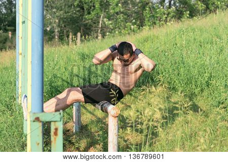 Strong young athlete. Strong young athlete is engaged in on an abandoned sports field. Exercise for abdominal muscles. Man shakes his stomach muscles. Athlete Outdoors. Toned image.