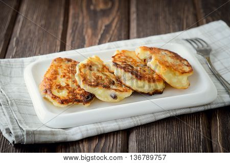 Homemade cottage cheese pancakes with raisin on a wooden background