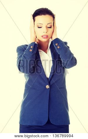 Attractive businesswoman covering her ears