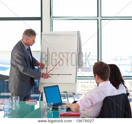 Senior businessman reporting to sales in a presentation with his colleagues
