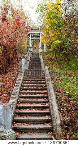 Old stairs to the gazebo in autumn park among yellow and red trees