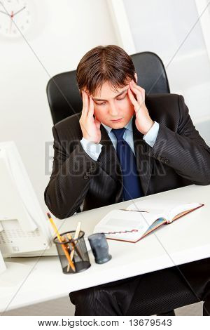 Stressed modern businessman sitting at office desk holding his head and worrying