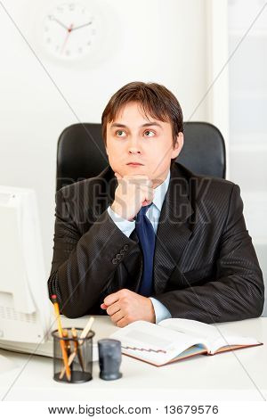 Thoughtful young business man sitting at desk and planning timetable in diary