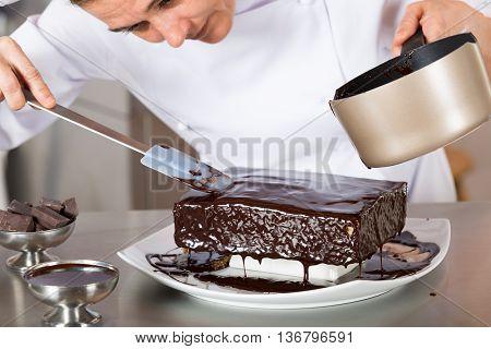 Pastry chef decorating cake yolk and cream