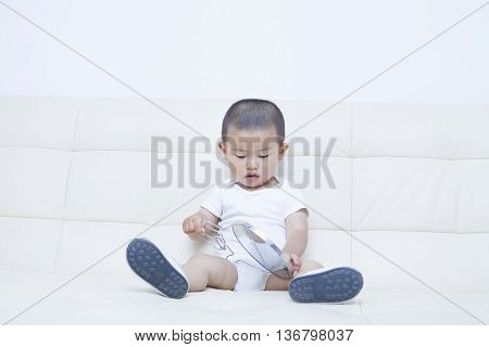 Cute Chinese Baby Boy Playing A Mirror In Sofa