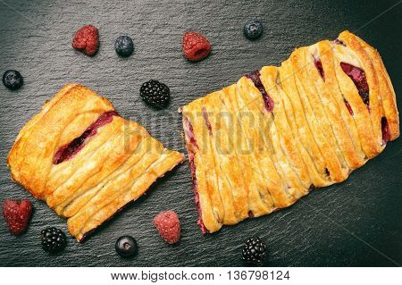 Sweet puff pastry with raspberries, blueberries, blackberries and creme cheese on black background.