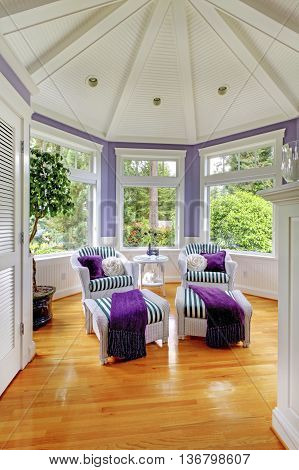 Vaulted Ceiling Living Room In Purple Tones With Two Stripped Armchairs..