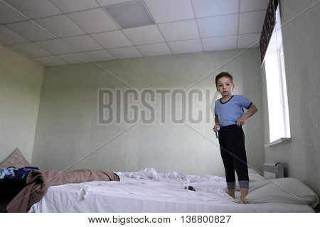Child Standing On Bed