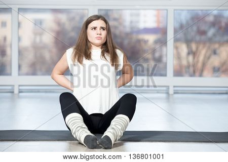 Portrait of injured unhappy fit young beautiful woman sitting in sports club touching her back after working out in class suffering from backache feeling pain full length