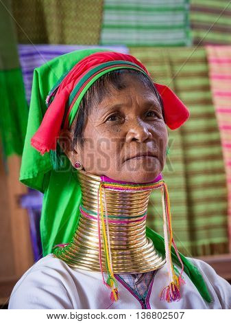 INLE LAKE MYANMAR - JANUARY 14 2016: Padaung Tribal woman poses for a photo in Inle lake Myanmar Burma The Padaung-Karen long-necked tribe women are minority of Myanmar.