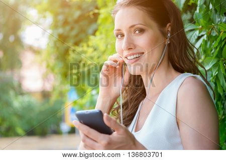 Cute brunette girl listening to music or audio book with headphones outdoors on a Sunny day. Image with lens flare effect