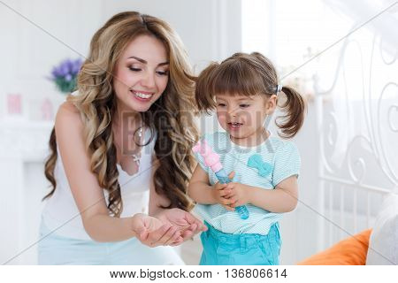 Happy young mother,blonde with long curly hair playing with her little daughter, a brunette, spend time in bright bedroom on a white bed,both dressed in white panties and white tops,having fun and smiling
