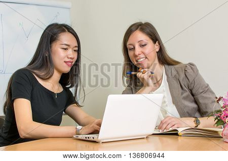 Two Business Woman Sitting By The Computer