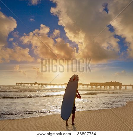 Daytona Beach in Florida shore with pier and unknown surfer walking USA